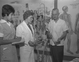 Practical nursing, 1968; two people standing next to a human skeleton model, student taking notes...