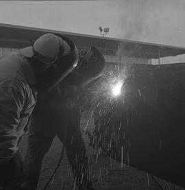 Welding, Nanaimo, 1968; two men wearing protective facemasks, one of the men welding
