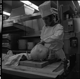 BC Vocational School Cook Training Course ; a student preparing a whole turkey to be cooked [1 of 2]