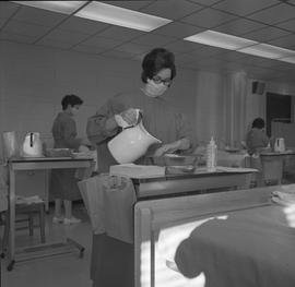 Practical nursing, Prince George, 1968; nurse wearing a face mask rinsing her hands ; people work...