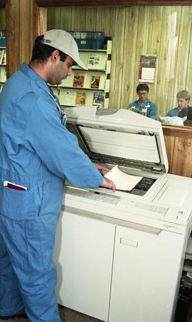 Student in coveralls using a photocopier [4 of 5 photographs]