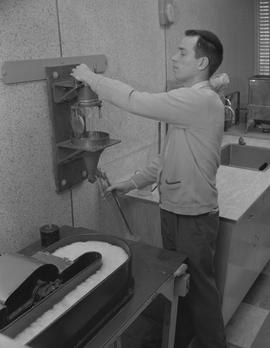 Forest Products, 1964; man pouring water from a large tap into a large test tube [1 of 2]