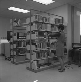 BCIT Burnaby campus library ; a staff member shelving a book