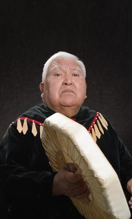 Bob George, First Nations elder, in First Nations garment playing an instrument [11 of 36 photogr...