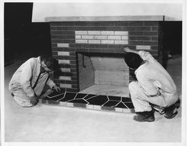 Bricklaying; two students cleaning mortar between the bricks of a fireplace