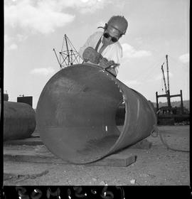 B.C. Vocational School image of a Boilermaker student cutting into a large metal pipe using a cut...