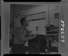 Logging, 1968; copy negative; picture of a man standing in an office and speaking into a micropho...