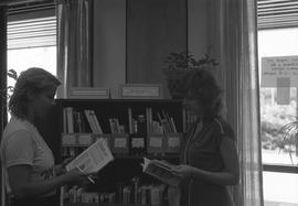 Two female students standing next to a book shelf reading books