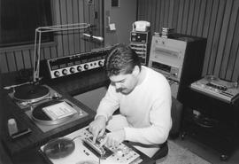 Broadcast Communications; man working in a radio production control room