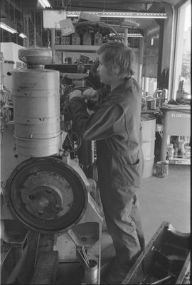 Pacific Vocational Institution ; a trade student working in a garage
