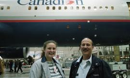 "Canadian women at work; woman and man inside a hangar under an airplane that that has a ""Can..."