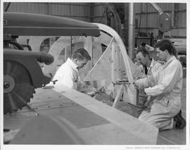 Three men building a boat frame in a workshop; Photo by the Division of Visual Education, Dept. o...