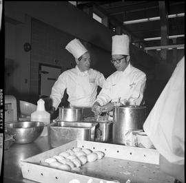 BC Vocational School Cook Training Course ; Mr. Buchli, cooking instructor, talking to a senior s...