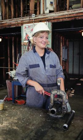 BCIT Women in Trades; plumbing, woman with pipe (cutting?) machine, September 1, 1995 [1 of 9 pho...
