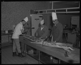 Meat cutting, 1968;  two people cutting pork ; one man sawing pork