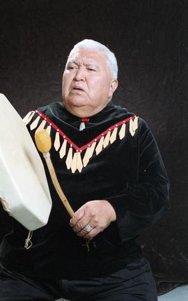 Bob George, First Nations elder, in First Nations garment playing an instrument [27 of 36 photogr...