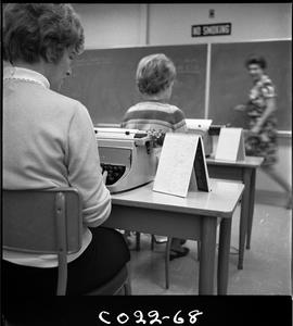 B.C. Vocational School; Commercial Program students sitting at desks in a classroom using a typew...