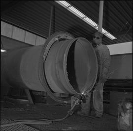 Welding, Nanaimo, 1968; man wearing protective goggles rotating a pipe that is being welded [1 of 2]
