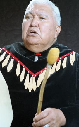 Bob George, First Nations elder, in First Nations garment playing an instrument [25 of 36 photogr...