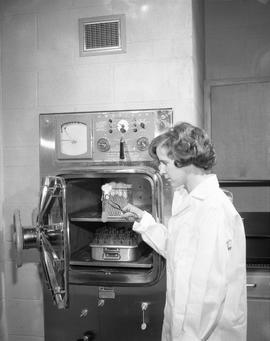 Food Processing Technology; woman in a lab coat removing test from food processing equipment