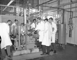 Mechanical technology, 1967; a group of men in lab coats looking at machinery [2 of 3]