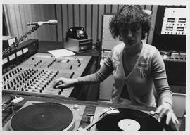 Broadcast Communication, 1980s; woman using turntables and control panel in the radio booth [2 of 2]