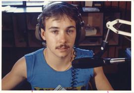 Broadcast Communication, 1987; man wearing headphones sitting in front of a microphone in a radio...