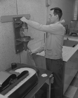 Forest Products, 1964; man pouring water from a large tap into a large test tube [2 of 2]