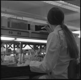 Medical laboratory technology, 1968; student in lab coat examining contents of a test tube [1 of 2]