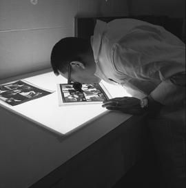 BCVS Graphic arts ; a man using a loupe to look at photographs on a light table
