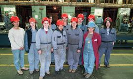 BCIT women in trades; plumbing, group shot of students in coveralls and hard hats standing inside...