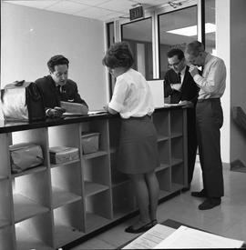 BCVS Graphic arts ; four people standing at a shelf and looking at papers [3 of 3]