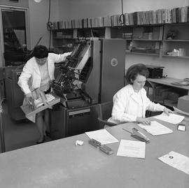 BCVS Graphic arts ; woman using a paper collator ; woman organizing papers at a desk