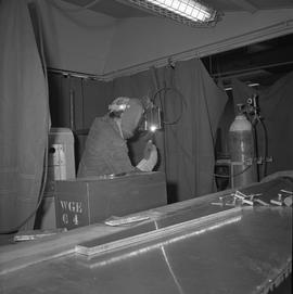 Welding, Terrace, 1968; man wearing protective goggles and gloves welding small pieces of metal ;...