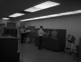 Business Management, 1964; man working with IBM 7330 computers, man standing at a computer printe...