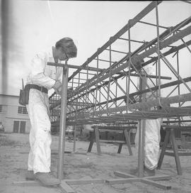 Structural steel, 1971; worker shaping wiring on a steel structure [2 of 2]