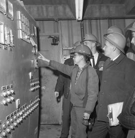 Forestry, Wood fiber BCIT tour, November 26, 1965; a man showing a group of men the control board...