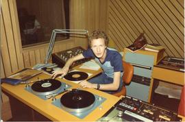 Broadcast Communication 1980s(?); man using turn tables in a radio booth