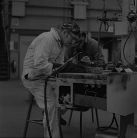 Welding, 1968; man looking at item he welded ; man working in background