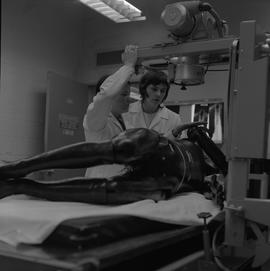 Medical radiography, 1968; two women in lab coats adjusting an x-ray machine with a manikin layin...