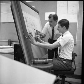 BC Vocational School drafting course ; instructor pointing at student's drawing while the student...