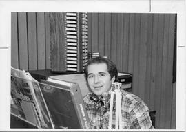 Broadcast Communication 1980s(?); male student sitting at the DJ desk in the radio control booth