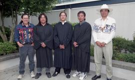 Three First Nations graduates in graduation robes standing with two First Nations men [2 of 2 pho...