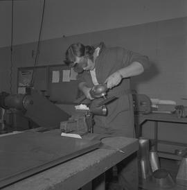 Sheet metal, 1968; man using a tool to buffer a piece of metal ; workshop in background