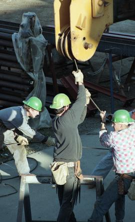 Ironwork, students wearing tool belts, hard hats and uniforms while using the tip a crane (?) [4 ...