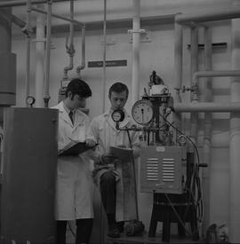 Mechanical technology, 1968; two men standing next to machinery and writing notes