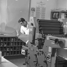 BCVS Graphic arts ; a man standing next to a printing press holding paper