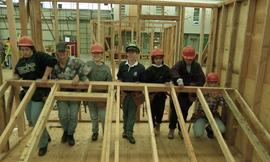 BCIT women in trades; carpentry, students wearing hard hats lifting a wooden frame inside a shop ...