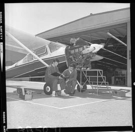BC Vocational School; Aeronautics students looking in a binder next to a small aircraft outside o...