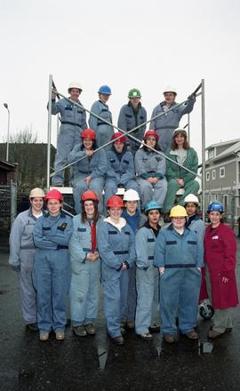 BCIT women in trades; plumbing (?), group shot of students in uniforms and hard hats surrounding ...